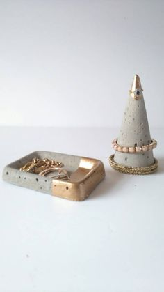 Add a bit of industrial charm to your home with these unique jewellery holders, hand cast in concrete, this useful cone and tray will keep your bracelets together and your rings and earrings safe. Choose from natural or concrete or add a metallic accent. Ring and Bracelet cone Approx 14 1/2 cm high x 6 1/2 cm across base. Jewellery tray Approx 12cm length x 8cm width x 2cm high