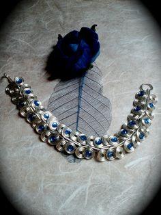 Ein wunderschönes Armband aus Silberdraht mit kleinen blauen Halbperlen. Die kleinen Schnecken sind aufwendig handgedreht und ineinander verflochten. Ein absolutes Unikat! Kein Armband sieht nach der Fertigung aus wie das andere!  Schreib uns an, wenn ihr eine andere Länge oder das Armband vielleicht in Kupfer oder auch patiniert möchtet. Auch die Perlenfarben sind individuell machbar.