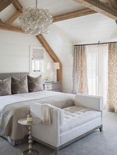 Elegant master bedroom with floor to ceiling shiplap,  exposed wood beams, white walls and grey carpet.