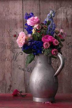 for a country look, put mixed variety flowers in an old pewter pitcher