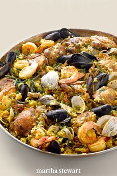 Heady with cognac and saffron our seafood paella is a glorious party platter that features mussels, clams, shrimp, calamari, and pork tenderloin in an exuberant celebration of good rice. #marthastewart #recipes #recipeideas #seafoodrecipes #seafooddinners #seafood Fish Recipes, Seafood Recipes, Dinner Recipes, Seafood Paella, Party Platters, Calamari, Mussels, Clams, Entrees