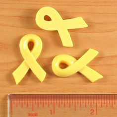 Yellow ribbon resin flat backs.  These are really cool for your crafts, like birthday/holiday card making, wedding deco, kids gift, sewing, scrapbooking, hair bows/clips, Cell phone deco, frame embellishments ect..  Size: As the 2nd photo Material: Resin Flatback Quantity: 10 pcs