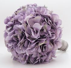 "Beautiful silk hydrangea blooms in the perfect shade of antique lavender make an elegant and romantic bridal bouquet. I can create it for you as shown or customize it to fit your color scheme. We can work together to create a custom silk flower wedding package for your entire wedding party! This custom silk flower bridal bouquet is 9"" in diameter and includes lavender silk hydrangea. The edge of the bouquet is finished with a collar of silver grey ribbon. The handle is wrapped in silver grey"