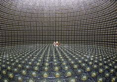 The Super-Kamiokande detector in Japan, an underground tank that holds 50 million liters of water, captures neutrinos that emanate from a particle accelerator nearly 300 kilometers away. When a neutrino hits the detector, it can produce charged particles, whose high speed through the water emits a flash of light, triggering phototubes mounted in the walls of the Super-K tank. The experiment investigates muon neutrinos transforming into electron neutrinos.