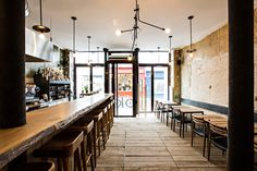 """One Yelp reviewernotes that the restaurant has a""""Brooklyn, Tokyo, Paris vibe."""" The ceiling pendant is similar to the Industrial Chandelier from Brooklyn/Charleston–based Workstead, and the live-edge bar is made from a single piece of wood."""