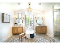 Newport CA master bathroom with cement tiles, round mirrors, rattan light fixture, freestanding tub, sunlight and a dose of magic. Love this space!