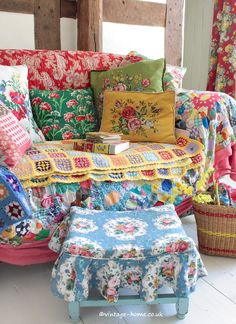 A cottage sitting room full of vintage colour.Sofa and stool dressed with pretty, colourful vintage fabrics.