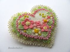 Hi! :) I first created this pin in 2010. Its always been one of my favorites, so here it is again! This sweet heart measures 2 1/2 across by 2 1/2 top to bottom. The layers are neatly stitched together with various beaded edgings. Flowers and leaves in pastel colors make this pin perfect for spring. A sprinkle of crystals adds just the right touch of sparkle! This is a clean, smoke free home. I ship my things within 3 business days of your payment. Your goodies arrive sweetly gift b...