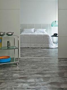 O piso laminado cinza-escuro Vintage (da alemã Kronotex, na Postigo) permitiu a este quarto de base branca aproveitar o aconchego da madeira com uma cor que foge do padrão. A arquiteta Maraí Valente assina o espaço.