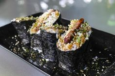 Spam Musubi: Thin strips of pan-fried spam get wrapped in steamed rice and nori. The key in contemporary spam musubi making is a plastic musubi maker, but you can also use an upside-down spam can to make the final shape.