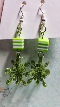 These adorable earrings are handmade by me. They each feature a bright green sparkly snowflake and a matching green bead attached with bright green jump rings. $4