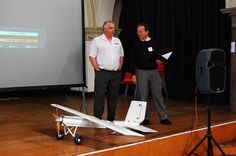 Eddie on stage with the Conventional Take-Off and Landing (CTOL) airframe, explaining how the first Open Source airframe works and is being further developed. Photo licensed Attribution-NonCommercial-ShareAlike 2.0 Generic (CC BY-NC-SA 2.0) by Andrew Back (carrierdetect).