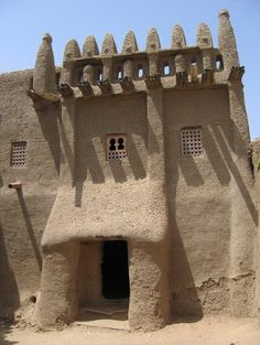 Facade of mud house in Djenne, Mali.  Notice how the door is low, making visitors stoop a bit to enter the house.  (Mud Architecture in West Africa)