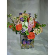 Floral cube filled with roses, stock, larkspur,  colorful flowers of summer
