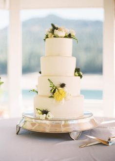White four-tiered wedding cake with flowers | Tim and Jess Photography