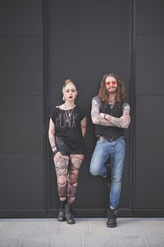 Portrait of punk hippy couple leaning against wall