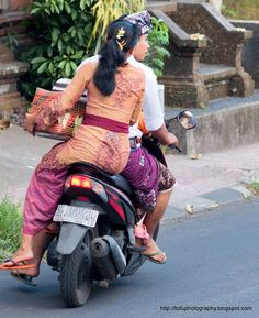 A Balinese man and woman dressed in traditional clothing on a motorbike on Jalan Suweat road in Ubud, Bali, Indonesia in June 2011