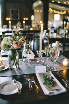 An elegant upscale barn wedding tablescape / centerpiece with taper candles, mason jars votives and gray linen runner on farm tables. Flowers included white, blush, peach and pink flowers like stock, peonies, garden roses, ranunculus, anemones, etc. Rustic chic.