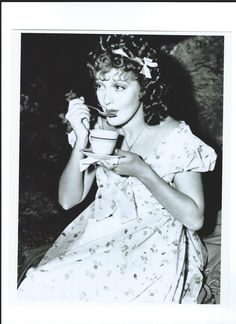 Jeanette MacDonald spooning her tea during a break in the filming of The Firefly - Escano Collection