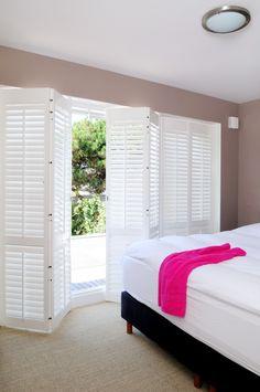 白い木製の折れ戸鎧戸で庭とつながるベッドルーム