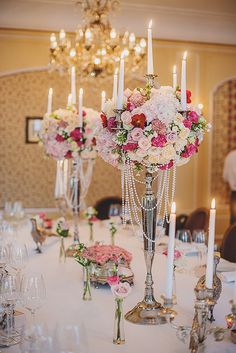 Elegant tall candelabra centerpieces decorated with roses, hydreangea, peonies and orchid and some draped pearls for good measure!