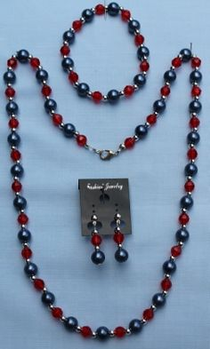 "This elegant 3 piece set has a slate blue round beads, with red faceted beads and silver coloured spacer beads. The bracelet is elasticated.   Necklace: 58cm (23"").  Bracelet: 17.5cm (6.8"").  Earrings: 1"" drop.  Materials used: Acrylic, silver coloured findings and elastic."
