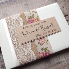 This pretty guest book is decorated with natural hessian/burlap and vintage ivory lace. Personalised with your details in typewriter and script style fonts in black ink, on a rustic card panel which is set in the centre over rose printed burlap ribbon.
