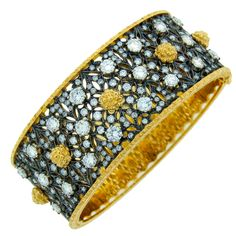 """MARIO BUCCELLATI Diamond, Silver & Yellow Gold Bangle Bracelet. Circa 1950's.   Signature Mario Buccellati open-work bangle bracelet created in Italy in the 1950's. The highlights of this bracelet are - typical Buccellati satin finish on yellow gold and amazing open-work on silver encrusted all over with round diamonds.  The bangle is 1"""" wide and fits up to 6.5"""" wrist."""