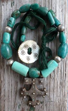 Ancient amazonite beads from Morocco and Mauritania featuring an old Tuareg cross and vintage hand forged sterling beads and an old Kuchi shell button closure.