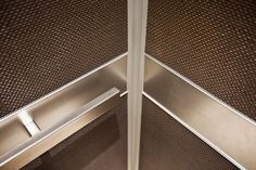 Rectangular Handrail in Satin Stainless Steel, shown in LEVELe-105 Elevator Interior with upper and lower panels in Bonded Bronze with Dark Patina and Charleston pattern; handrail panels in Stainless Steel with Seastone finish