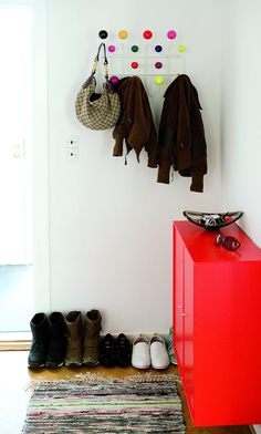 Colourful welcoming in the entryway with a red dresser and a playful coat rack.