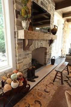 A stone fireplace and wood mantle add a charming touch to this living room. The post A stone fireplace and wood mantle add a charming touch to this living room. appeared first on Decoration. Rustic Fireplaces, Home Fireplace, Fireplace Remodel, Fireplace Design, Fireplace Ideas, Fireplace Stone, Rustic Mantle, Mantel Ideas, Country Fireplace