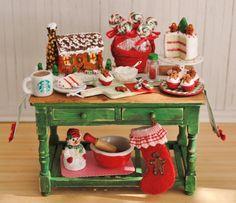 ~ Il sagit dun 01:12 Noël cuisson table avec un thème de pain dépice à léchelle. La table est peinte en verte avec une finition minable, et il a un haut de planche de pin. Sur le dessus de la table, il y a un chemin de table de Noël avec pompon rouge garniture. Il y a une maison de pain dépice avec neige brillant, les arbres, un trottoir de la menthe poivrée et un homme de pain dépice. Il y a un panier rouge rempli de tourbillon lollipops en couleurs de Noël. Il y a un gâteau de couche avec…