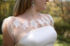 Sold on etsy, a piece of illusion tulle with lace applique that can be sewn to a strapless dress. $95