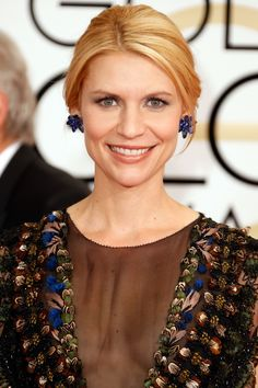 Danes played off the blue in her textured Valentino dress and earrings with a barely-there peek of glittery navy liner along the top and bottom lashes. Her hair was pulled back in a relaxed chignon, the result of twisting a low ponytail clockwise into a pretzel-like shape. Getty Images  - HarpersBAZAAR.com