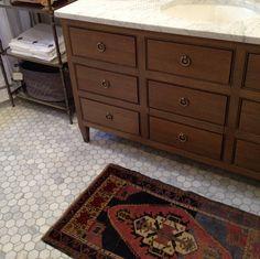 Classic chest of drawer look under marble sink on top of Carrara hexagon floor