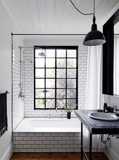 The black-metal, factory-style bathroom window was designed to open up completely, 'so when it's cold outside, it feels like you're in an outdoor spa'; retrouvious.com has a good stock of salvaged windows.