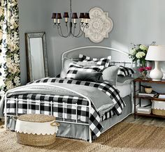We love to take two opposing patterns and blend them together. An overscale floral and a large buffalo check balance each other out in this black and white bedroom.