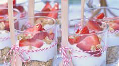 fruit and yogurt parfait with strawberries granola and wooden spoons with red and white string