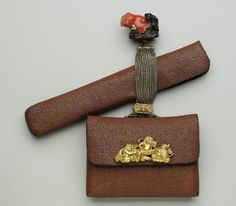 Tobacco-pouch and pipecase; netsuke in the form of a koronbo with a giant piece of coral; kanamono in the form of a seated samurai and two oni; rectangular gold filigree ojime; silver chains  Japanese, Meiji era, mid to late 19th century (before 1889)  By Serizawa Ryumin, Japanese, born in 1826  By Miwa, Japanese, MFA