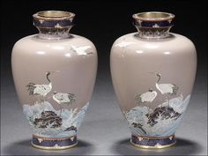 A pair of cloisonné vases Meiji Period. Each of ovoid form and worked in silver wire with cranes in flight and perched on a wave-lashed rock, on a mauve ground, unsigned; two wood stands.