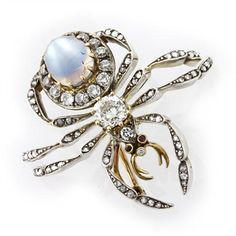 A Victorian moonstone and diamond spider brooch, the body composed of an oval shaped cabochon-cut moonstone cluster, the moonstone estimated to weigh 4.1 carats, set to a cushion-cut diamond abdomen, weighing approximately 0.6 carats, to a rose-cut diamond head with faceted ruby eyes and finely modelled legs set with rose-cut diamonds, all set in silver on a yellow gold back, measuring approximately 3½cm, gross weight 13 grams, circa 1890.