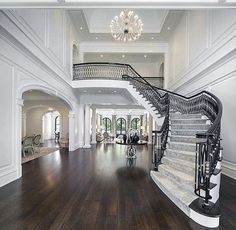 Grand staircase of luxury mansions with double height foyer, custom ironwork railing details, paneled walls, cathedral ceiling and decorative chandelier Dream House Interior, Dream Home Design, Home Interior Design, House Design, Ikea Interior, Foyer Staircase, Staircase Design, Chandelier Staircase, Floating Staircase