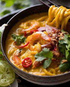 Soupe thaïlandaise à la noix de coco avec crevettes, crevettes et nouilles dans un bol rustique, prête à être mangée