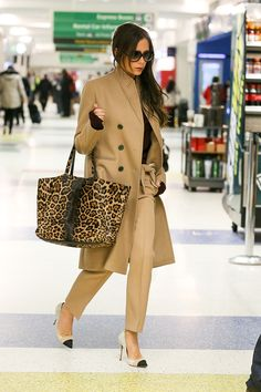 Victoria Beckham in a camel coat + burgundy sweater + khaki trousers + two-tone heels + leopard-print tote