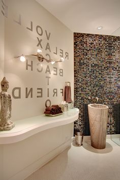 Powder room, Stone Forest Travertine Solid sink, Glass mosaic wall, Wall mounted faucet and stenciled letters repeating what is on the other side of the wall