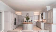 by Farrow & Ball. The Cabinets were Elephants Breath, and the Island was Chemise (no longer available), I believe the walls were painted in Cornforth White.