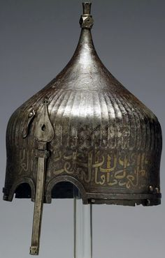 Ottoman or Persian turban helmet, 15th to 16th century, steel with silver inlay, A warrior would have worn this helmet over a cloth turban. He would have been confident of being safeguarded in battle by the writing around the helmet's rim. The inscription from the Qur'an is garbled however, indicating that its Iranian maker may not have known Arabic, but it was enough to invoke the protective power of God's word. Walters Art Museum, Baltimore Maryland. 38.5 × 23.4 cm (15.2 × 9.2 in) (h. x…