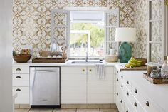 In a different Harbour Island house, the designer placed custom-made, swing-in casement windows from France in the kitchen, opening it to the outdoors. The walls are covered in Cuban tiles.