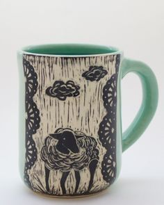 This handmade pottery mug is etched with a lamb and fluffy clouds. It is etched by hand with a design that looks like a woodcut. Patricia makes these in her California studio and ships throughout US.